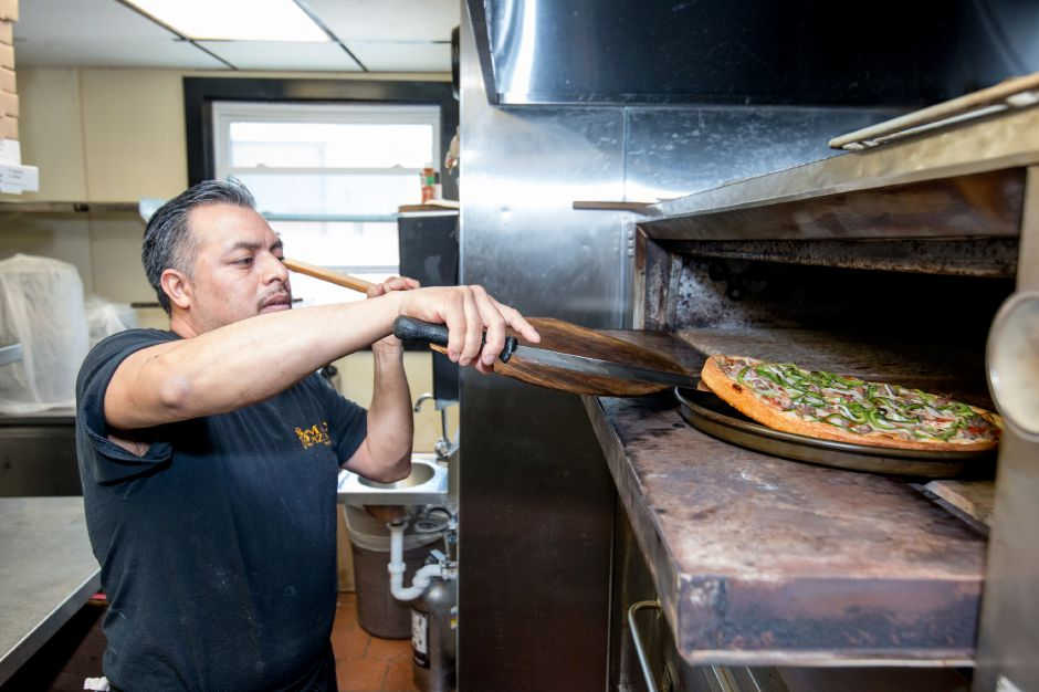 Juan Carlos, of Plainville, takes a pizza out of the ovens at Max Pizza 6 in Southington. The restaurant had its grand opening Thursday.  Devin Leith-Yessian, Record-Journal
