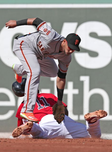 San Francisco Giants second baseman Cristhian Adames, top, steps on the foot of Boston Red Sox