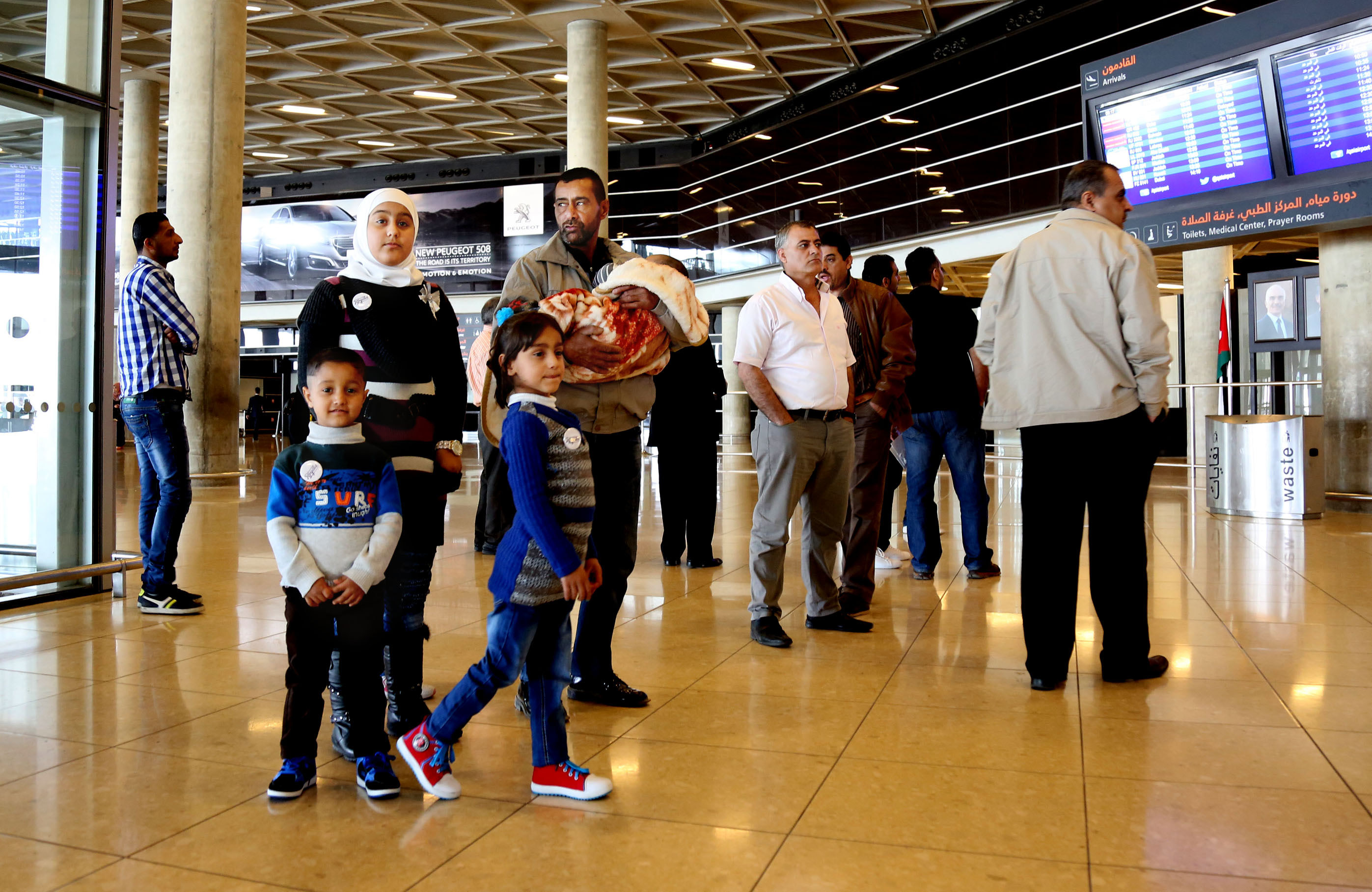"Syrian refugee Ahmad al-Abboud, center, waits with his family at the International Airport of Amman, Jordan, Wednesday, April 6, 2016. The first Syrian family to be resettled to the U.S. under its speeded-up ""surge operation"" departed to the United States Wednesday from the Jordanian capital, Amman. Al-Abboud, who is being resettled with his wife and five children, said that although he is thankful to Jordan  where he has lived for three years after fleeing Syria"