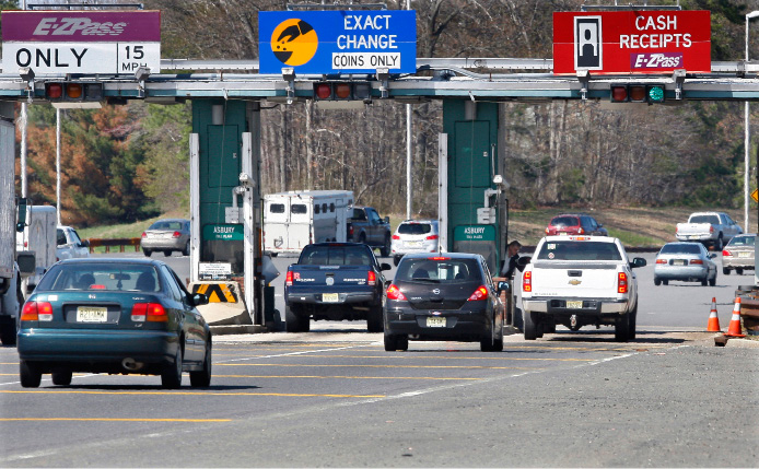 FILE- In this April 21, 2011, file photo, cars pass through the toll booths at the Garden State Parkway