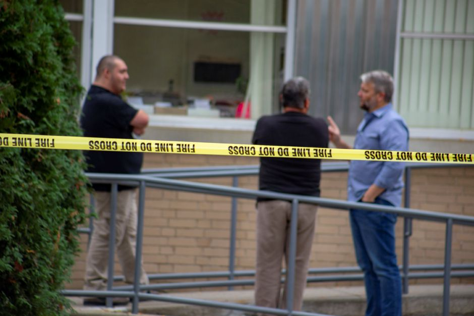 Employees from The Money Source talk outside the building while firefighters investigate a report of a suspicious substance in the mail room of the South Broad Street business Sept. 21, 2018. | Richie Rathsack, Record-Journal