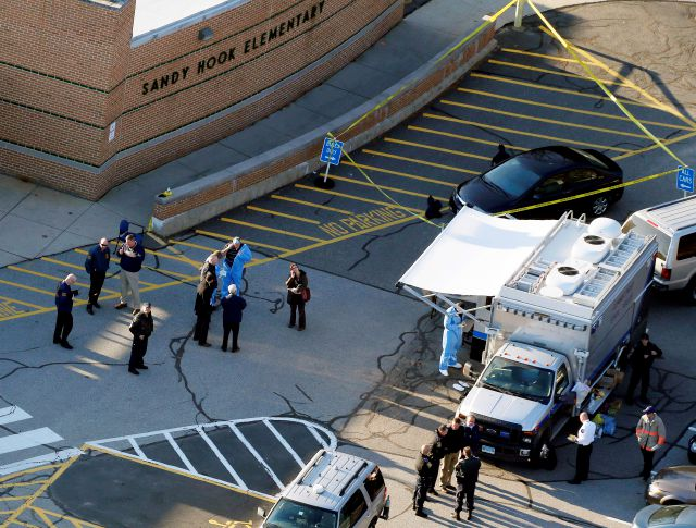FILE - In this Dec. 14, 2012, file photo, officials stand outside of Sandy Hook Elementary School after a shooting in Newtown, Conn. Connecticut State Police are planning to release a report assessing the agency's response to the 2012 massacre at Sandy Hook Elementary School. The after-action report is expected Friday, Jan. 12, 2018. (AP Photo/Julio Cortez, File)