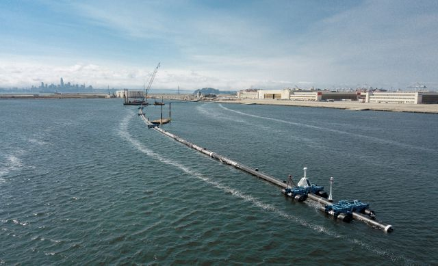 In this Monday, Aug. 27, 2018 photo provided by The Ocean Cleanup, a long floating boom that will be used to corral plastic litter in the Pacific Ocean is assembled in Alameda, Calif. Engineers will deploy a trash collection device to corral plastic litter floating between California and Hawaii in an attempt to clean up the world