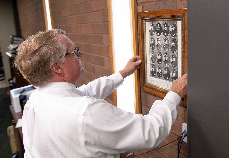Chief Jeffry Cossette hangs a 113-year-old framed photograph of Meriden police department members donated to the police department by Sheri DeLuca, Wed., July 24, 2019. The Meriden Historical Society coordinated the donation of the photograph during a ceremony held at the police station on Wednesday. The photograph was found in the belongings of Dan DeLuca, a former teacher and local historian, by his daughter after he died three years ago. Dave Zajac, Record-Journal