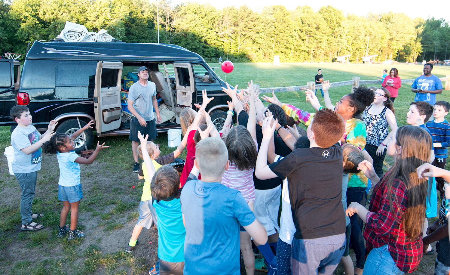 Kids try to grab a balloon thrown by Southington physical education teacher Eric Korp at the Southington Drive-In