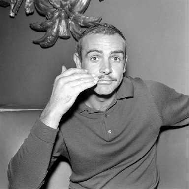 "Scottish actor Sean Connery brushes down his new moustache at a reception in London, United Kingdom given to launch his new film on Sept. 1, 1964, and to introduce the facial adornment. The mustachioed actor will star as a court-martial's Regiment Sergeant Major in ""The Hill"", which is to be shot at the Boreham Wood film studios in Hertfordshire and on location in Spain. (AP Photo/Bob Dear)"