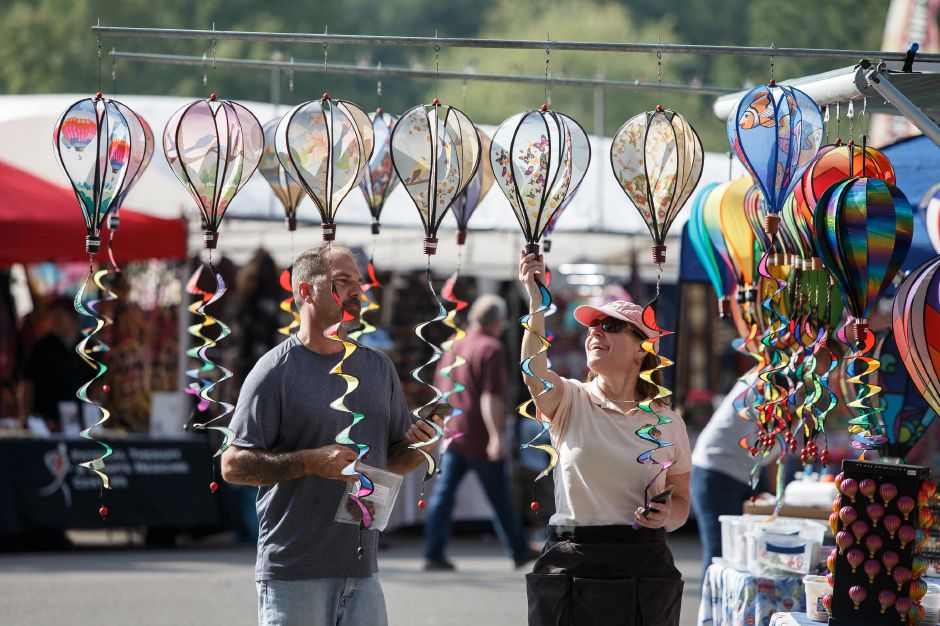 Kathy Reynard of Full A Haot Air right shows Joe Dube a balloon mobile Friday during the 34th Annual Plainville Balloon Festival at Norton Park in Plainville August 24, 2018 | Justin Weekes / Special to the Record-Journal