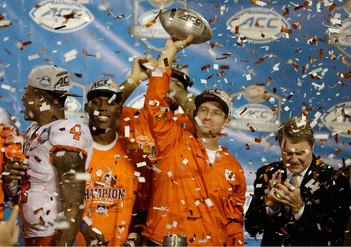 Clemson head coach Dabo Swinney raises the Atlantic Coast Conference championship football Sunday in Orlando, Fla., after the Tigers defeated Virginia Tech 42-35. | Associated Press