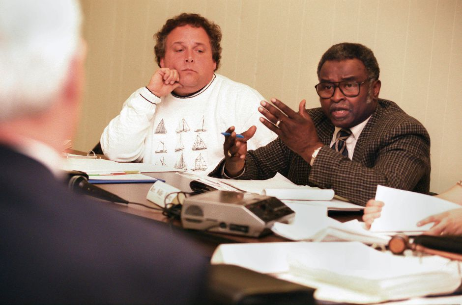 RJ file photo - The. Rev. Willie Young, right, questions Meriden Mayor Joseph J. Marinan r., while Kevin Danby, center, and other ponder the future of the Mills Memorial Apartments Dec. 15, 1998. The meeting took place in the Mills Community Room.