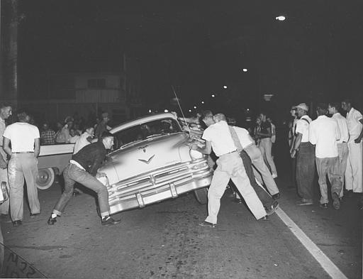 An angry mob tries to overturn a car carrying blacks passing through on U.S. Highway 25-W in Clinton, Tenn., Aug. 31, 1956.  The driver sped away before the doors were opened.  The mob was motivated by the White Citizens Council leader who spoke against integration at Clinton High School, an all-white school which has been a scene of violence this week.  (AP Photo/Gene Herrick)