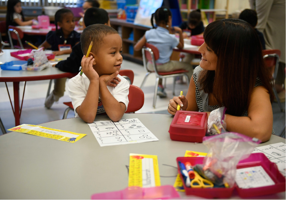 In this Friday, Sept. 29, 2017 photo, Elionet Saez Martin, of Puerto Rico, left, works with his kindergarten teacher Rachael Leupold, right, at Chamberlain Elementary School in New Britain, Conn. As Hurricane Maria churned toward Puerto Rico, Elionet