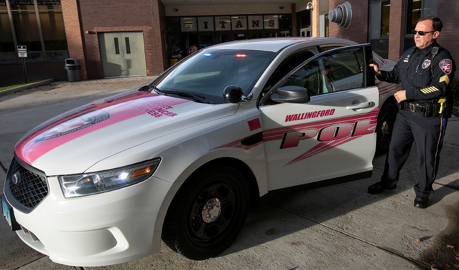"Sgt. David Blythe shows a police cruiser that has been ""wrapped"" in pink and displays the lettering ""Breast Cancer Awareness"" while at Sheehan High School, Wednesday, Oct. 3, 2018. Dave Zajac, Record-Journal"