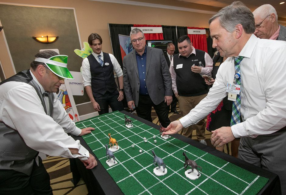 Quinnipiac Chamber of Commerce Business Development Executive Gary Ciarleglio, left, heads a horse race game as Michael Nesti, of Wallingford, right, rolls the dice in hopes of advancing his horse during the casino-themed Quinnipiac Chamber of Commerce Annual Business Showcase at the Best Western in North Haven, Thurs., Apr. 4, 2019. Nesti is Marketing Manager for Masonicare at Chester Village. Dave Zajac, Record-Journal