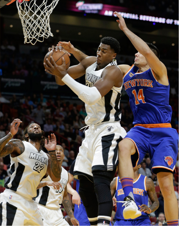 Miami Heat center Hassan Whiteside, left, grabs a rebound over New York Knicks center Willy Hernangomez (14) during the first half of an NBA basketball game, Tuesday, Dec. 6, 2016, in Miami. (AP Photo/Lynne Sladky)