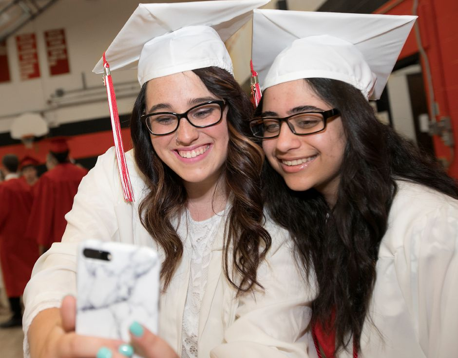 Graduates Mackenzie Cerrone, 18, left, and Mahtab Kakhodaverdi, 18, take a selfie before the start of graduation ceremonies at Cheshire High School, Thursday, June 21, 2018. Dave Zajac, Record-Journal