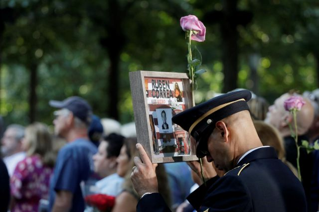 A man holds a photo of a victim during a ceremony marking the 18th anniversary of the attacks of Sept. 11, 2001, at the National September 11 Memorial, Wednesday, Sept. 11, 2019, in New York. (AP Photo/Mark Lennihan)