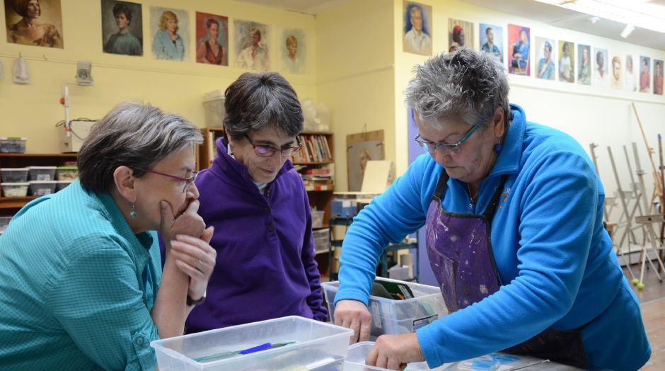 Marylou Shoemaker (far left) and Andrea Stelma (middle) watch as instructor Christine Webster (far right) demonstrate how to fuse pieces of glass.