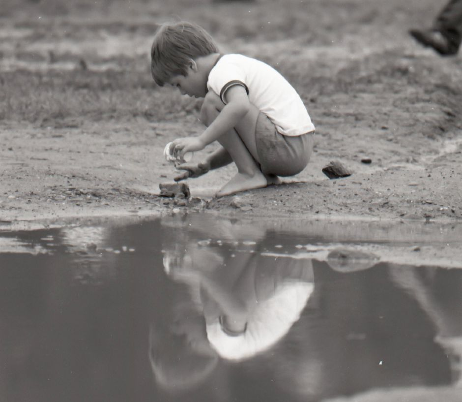 A child plays near a puddle after a rain storm passed through Meriden, 1975.