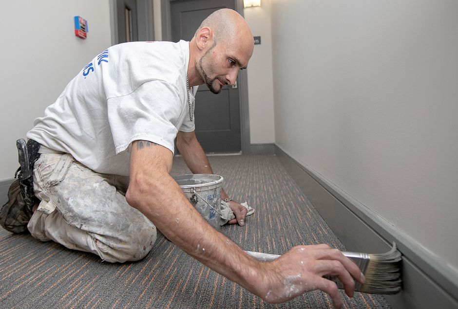 Painter Daniel Berk cuts in the trim along the main hallway of the newly constructed Parker Place Apartments in Wallingford, Tuesday, Sept. 11, 2018. Construction is continuing on Parker Place Apartments while the first tenants move in. Dave Zajac, Record-Journal