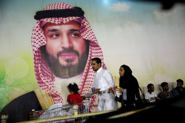 A Saudi family walk past a giant poster of Saudi Crown Prince Mohammed bin Salman, at a shopping mall in Jiddah, Saudi Arabia, Sunday, Sept. 15, 2019. The weekend drone attack on one of the world