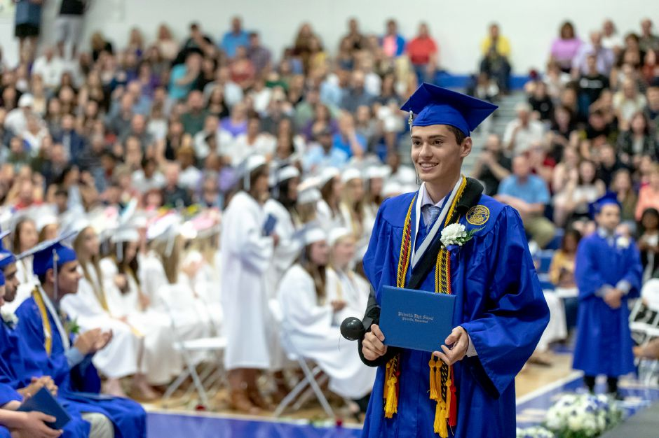 A student poses with their diploma during the Plainville High School graduation ceremony, held in the school