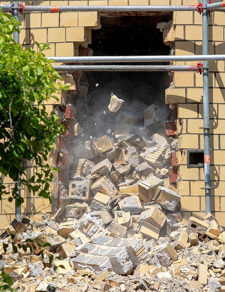 Bricks tumble down the interior of a smokestack as it is dismantled from the top on the former Meriden-Wallingford Hospital property on Cook Avenue in Meriden, Thursday, August 23, 2018. Dave Zajac, Record-Journal