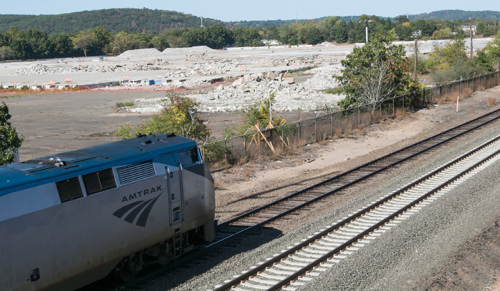 An Amtrak train heads north past the future site of an Amazon distribution center and warehouse facility at 415 Washington Ave. in North Haven, a 168 acre property off Route 5 formerly used by Pratt & Whitney, Thursday, Oct. 12. | Dave Zajac, Record-Journal
