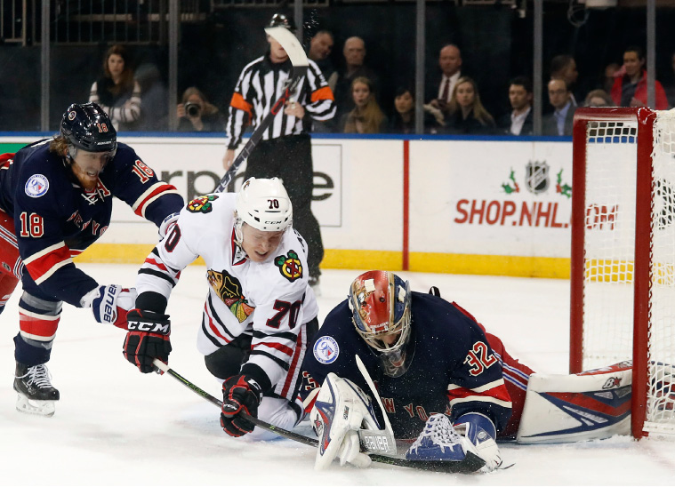 New York Rangers goalie Antti Raanta (32) falls on the puck as Chicago Blackhawks center Dennis Rasmussen (70) tries to score with New York Rangers defenseman Marc Staal (18) defending during the first period of an NHL hockey game, Tuesday, Dec. 13, 2016, in New York. (AP Photo/Julie Jacobson)