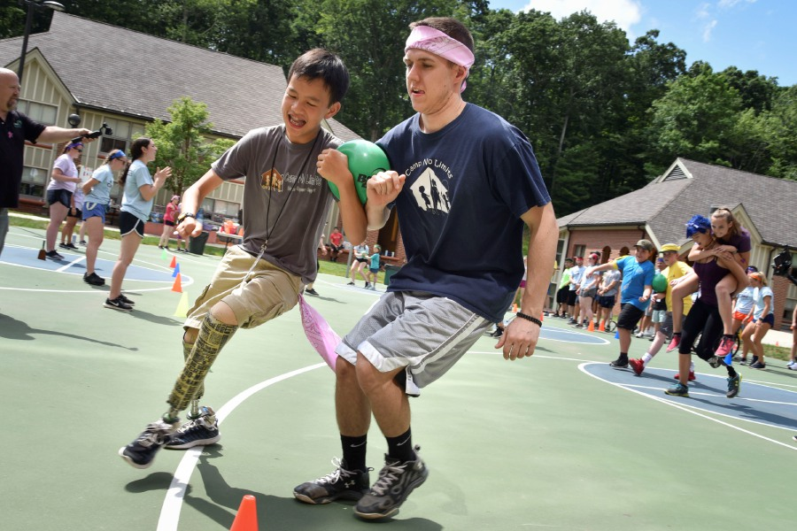 Matthew Reid, 12, of Cheshire, and a mentor take part in Camp No Limits' field day on the Quinnipiac University York Hill Campus in Hamden on Friday. The four-day, overnight camp aims to increase the functional independence of children living with limb loss.
