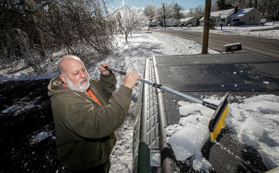 Mike Raccio, of Meriden, chops ice off the cover of his truck bed at his West Main Street residence on Tuesday.