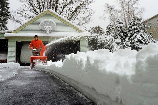 A Portland, Maine resident uses a snowblower to clear snow during a nor