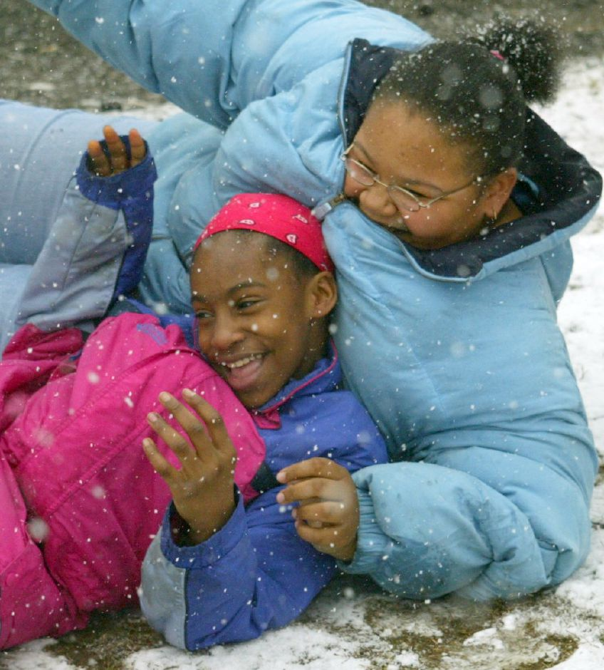 Jasmine Wesley, 11, left and friend Shaneshia Jordan, 14, both of Meriden, wrestle around in the snow at their residence on Miller Ave. in Meriden Tuesday afternoon March 16, 2004. Both were dismissed early from school due to the weather of the snow.