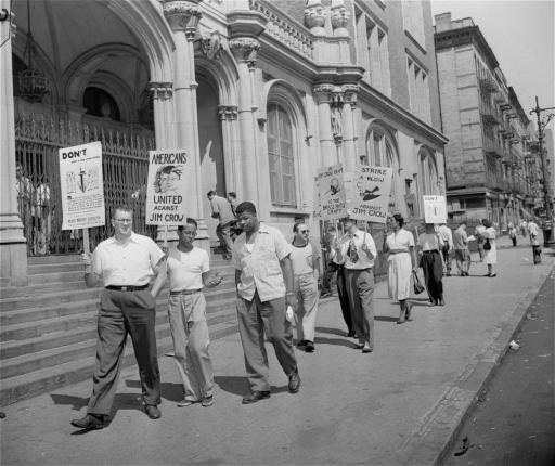 Pickets carrying placards bearing anti-draft slogans parade in front of Haaren High School, New York, August 30, 1948, one of the city