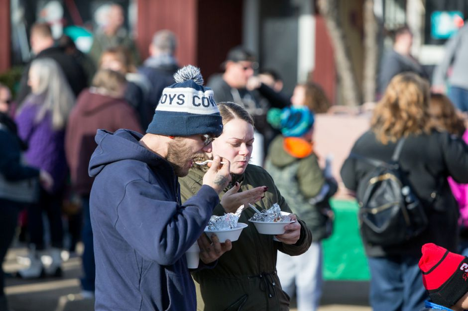 Ronald Berube and Monique Nadeau enjoy some baked apples Saturday during Christmas in the Village on Main Street in South Meriden December 1, 2018 | Justin Weekes / Special to the Record-Journal