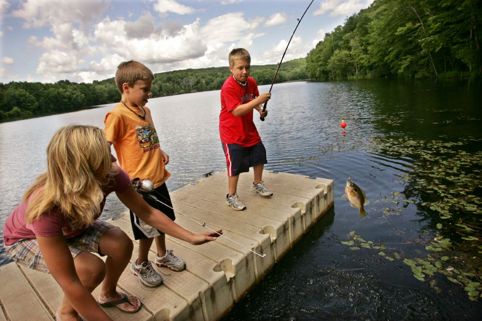 Crescent Lake ranks third on TripAdvisor.com's list of things to do in Southington. In this file photo, Mark Meade, 10, of Southington, right, pulls in a sunfish while fishing with brother Jack, 7, and mother Lorraine on July 8, 2009. (Dave Zajac photo)