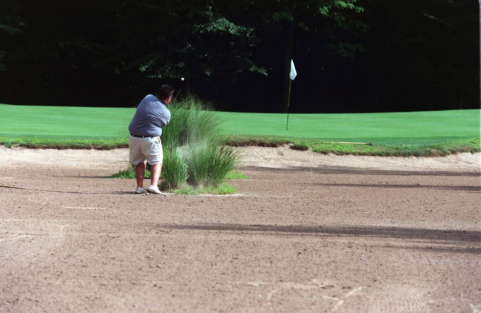 Jeff Smythe, of Bristol, hits out of the huge sand trap on the 15th hole of Pine Valley Golf Course Tues., Aug. 10 1999 in Southington.