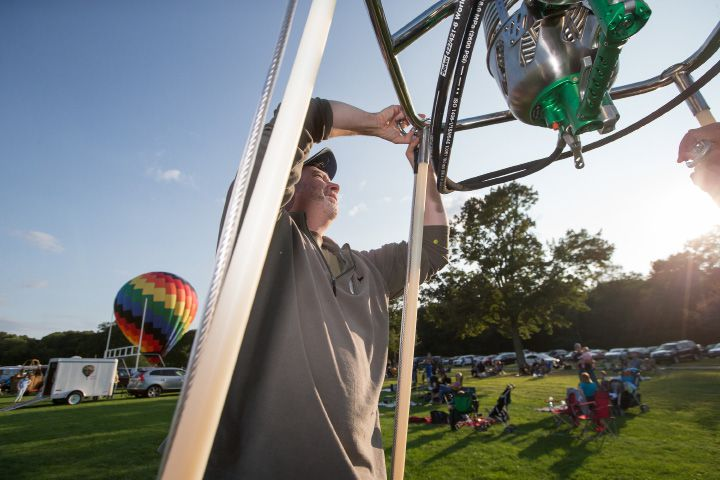 "Nicj Murphy of Bethlehem attaches the burner to ""Trinity II"" before the balloon glow Friday during the Plainville Fire Company 33rd Annual Hot Air Balloon Festival at Norton Park in Plainville Aug. 25, 2017 