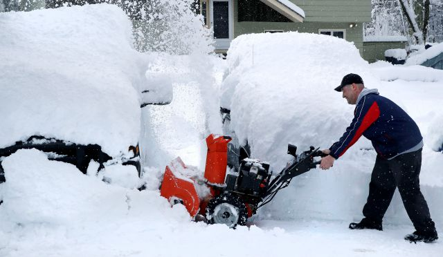 John Visco clears snow from around the cars in his driveway in Derry, N.H., Thursday, March 8, 2018. An overnight, winter storm blanketed the area with over a foot of snow. (AP Photo/Charles Krupa)