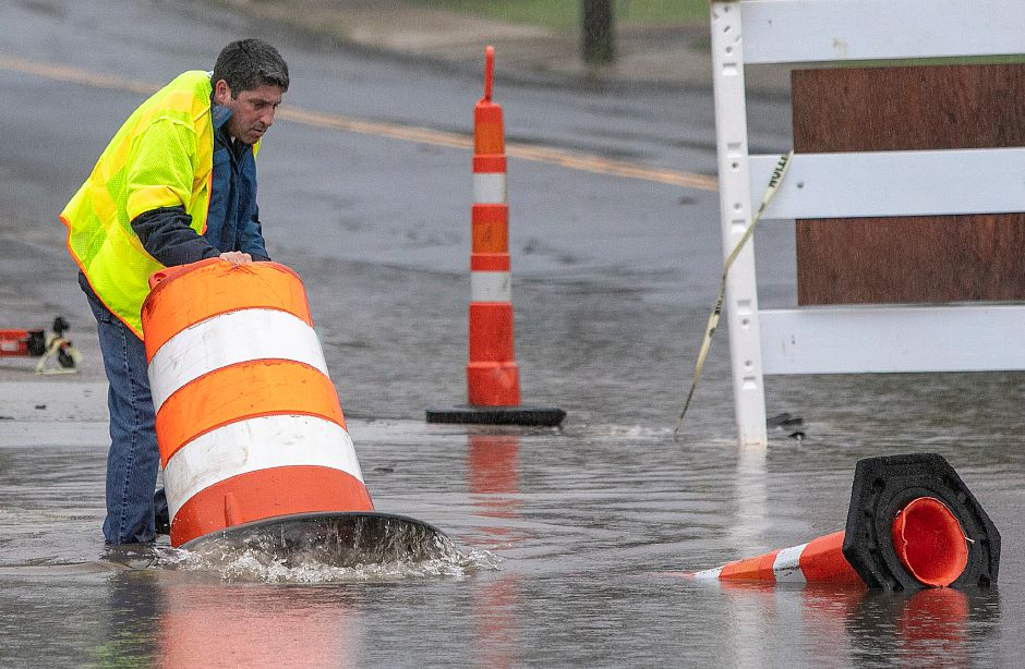 Meriden Public Works Director Howard Weissberg repositions a construction barrel in flood waters at the intersection of Pratt and Center Streets in Meriden, Tuesday, Sept. 25, 2018. Heavy rain Tuesday evening closed roads and flooded basements of local homes. Dave Zajac, Record-Journal