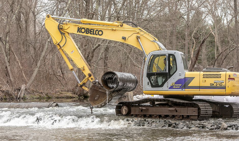 A worker maneuvers an excavator Friday to remove a section of 30-inch pipe from the Quinnipiac River during the final phase of the Quinnipiac River barrier removal project in Meriden. Dave Zajac, Record-Journal