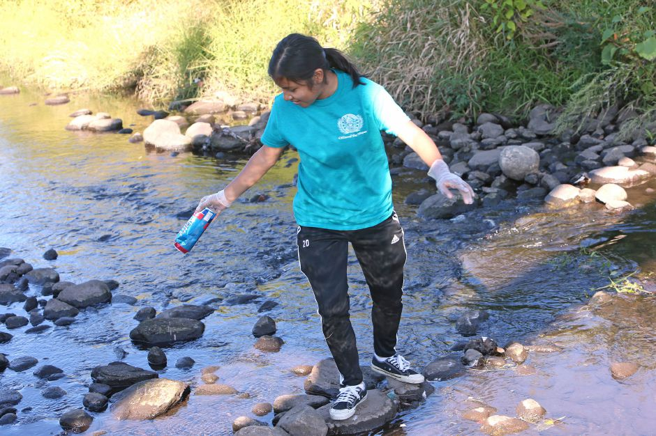 Nayely Galvez-Salazar, a Platt High School senior, retrieves trash from the middle of the river in the Meriden Green during the annual Community Cleanup Day on Saturday, Sept. 21, 2019. Emily J. Tilley, special to the Record-Journal.