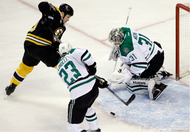 Dallas Stars defenseman Esa Lindell (23) sweeps the puck away before Boston Bruins left wing Matt Beleskey, left, can attempt a shot against Stars goalie Antti Niemi (31) during the first period of an NHL hockey game, Thursday, March 30, 2017, in Boston. (AP Photo/Elise Amendola)