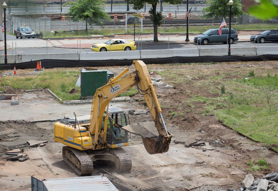 A worker in an excavator rips up pavement from the parking lot at 24 Colony St. in Meriden Thursday June 18, 2015. | Richie Rathsack/Record-Journal