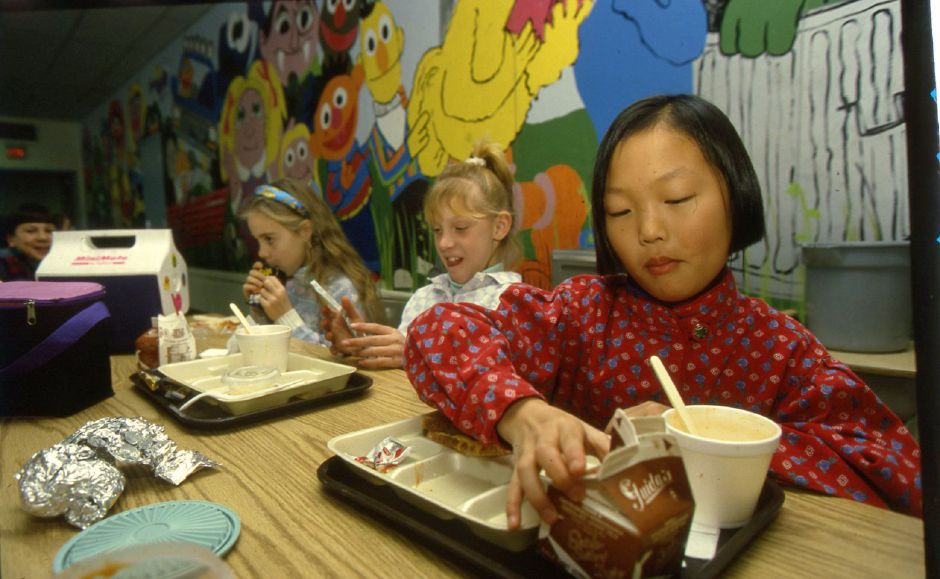RJ file photo - Kate Fritzel, Stephanie Whithworth and Brynn Gannon, fourth graders at the Stevens School, eat a lunch that featured dinosaur-shaped Tater Tots Jan. 13, 1994.
