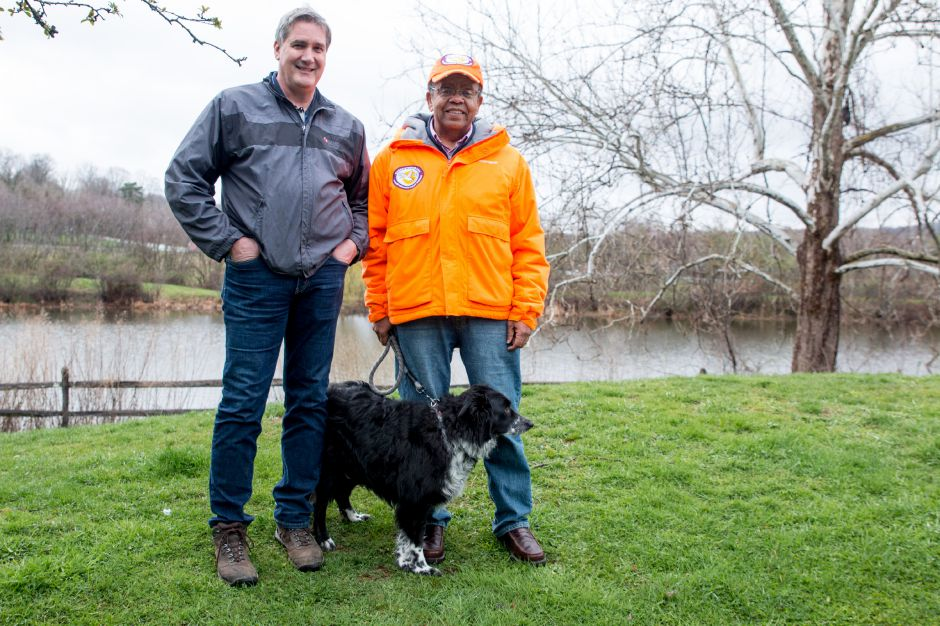 Alan Kendrix, right, stands with John Lyman, vice president of Lyman Orchards and his dog, Bear. Kendrix is owner of No Geese Today, a company which uses dogs, like Bear, to haze Canada geese at locations like the orchards.