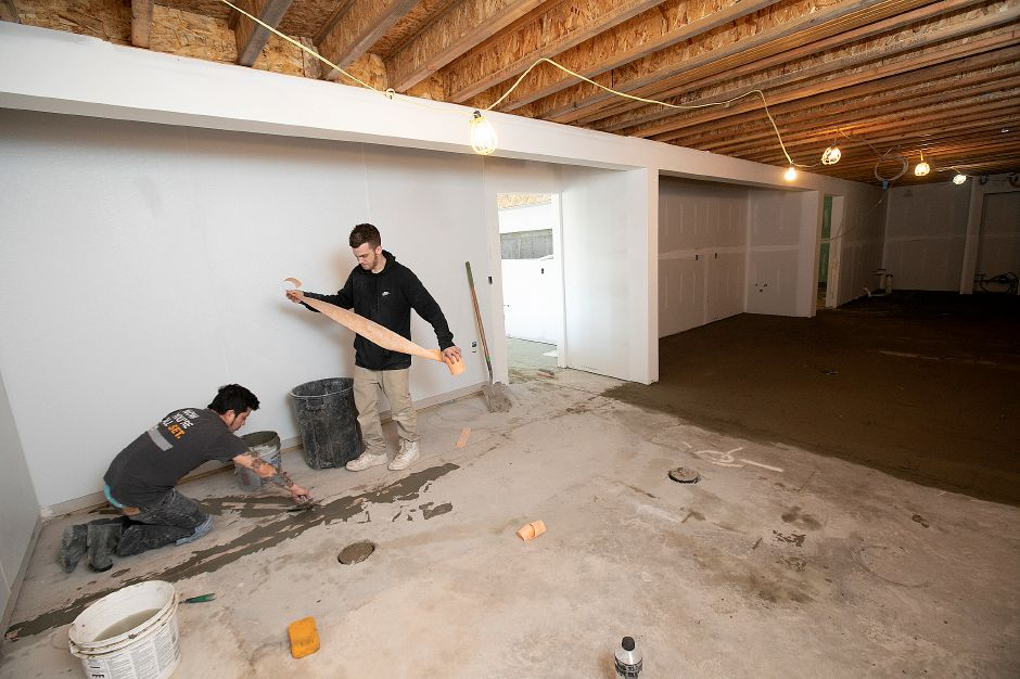 Soel Galvez, left, and Tom Martino, working for West Haven based Walter Hurley Tile and Marble, prepare a floor for tiling as interior construction continues on Huxley