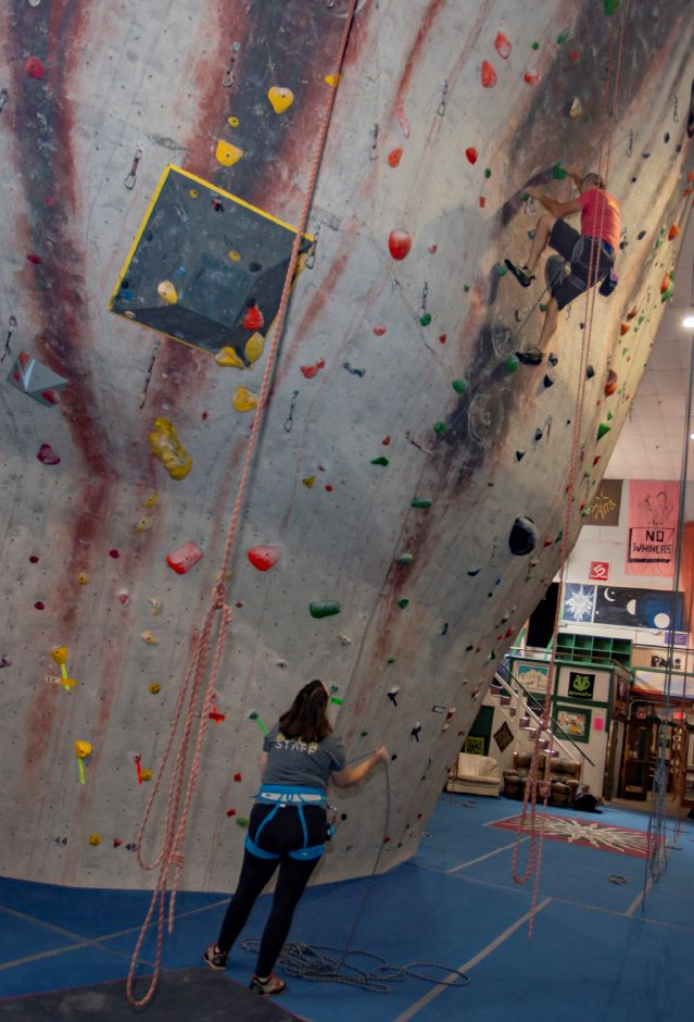 Brien Roscetti, owner looks for his next grip on the climbing wall at Prime Climb in Wallingford as manager Kristina Godfrey spots him Aug. 20, 2018 at the Quinnipiac Avenue facility. | Richie Rathsack, Record-Journal
