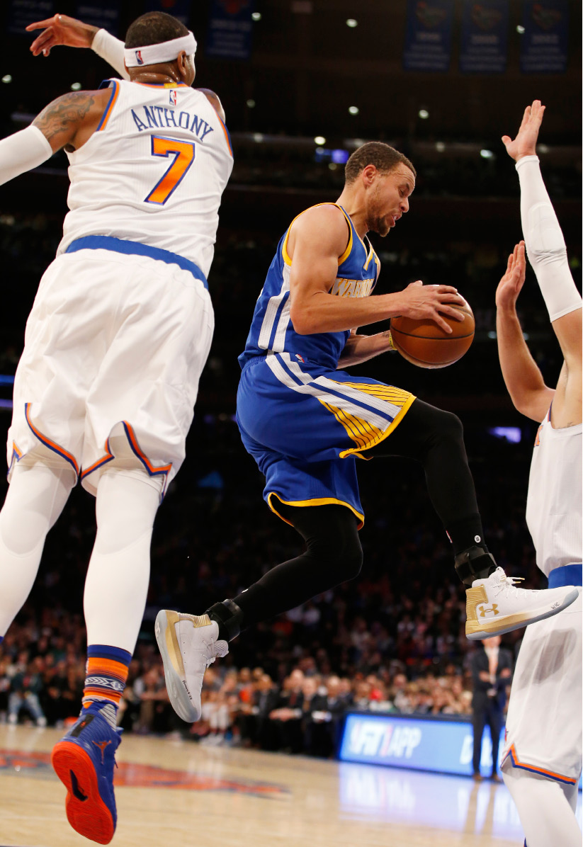 Golden State Warriors guard Stephen Curry (30) jumps through two New York Knicks defenders, including Carmelo Anthony (7), in the first half of an NBA basketball game at Madison Square Garden in New York, Sunday, March 5, 2017. (AP Photo/Kathy Willens)