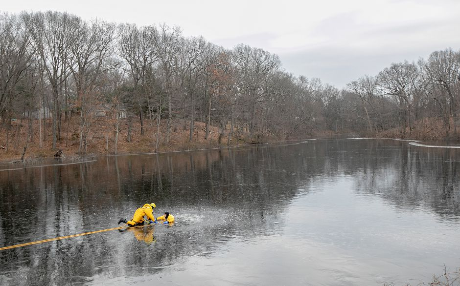 Southington firefighters Daniel Comen, left, and Derek Dion practice a cold water rescue at a pond off Mandel Drive in Southington on Wednesdsay. Nearly all town firefighters will participate in the training.Photos by Dave Zajac, Record-Journal