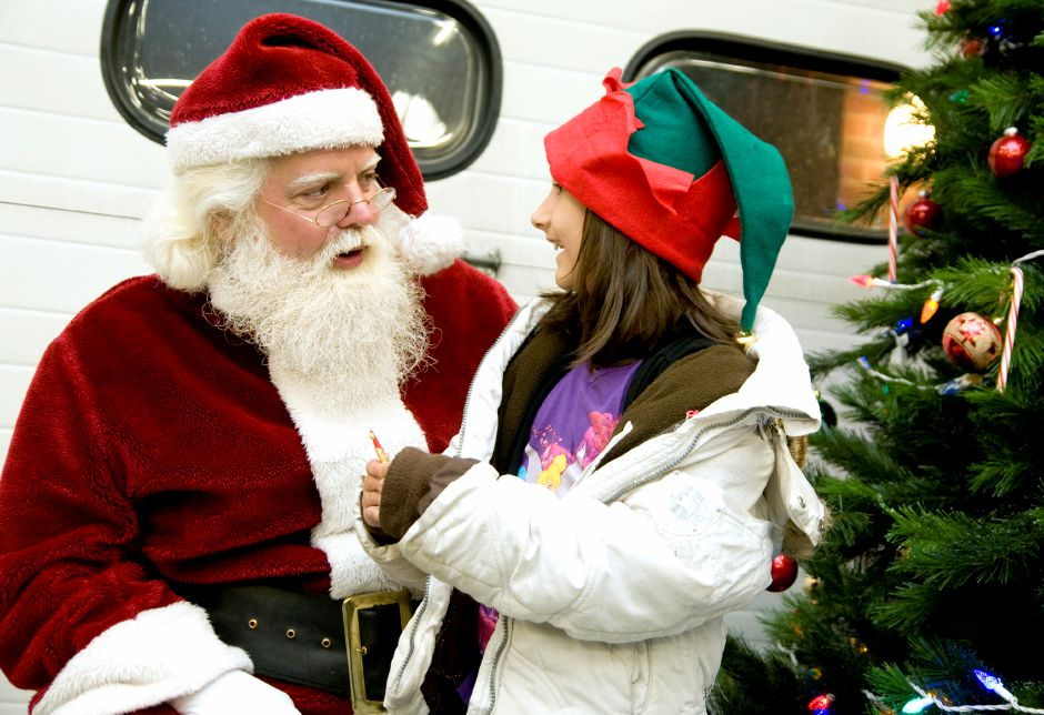 Santa Claus listens as Brianna Bajram,7, from Southington, tells him what she wants for Christmas during the Christmas in the Village event in downtown Plantsville, December 1, 2011. (Sarah Nathan/Record-Journal)
